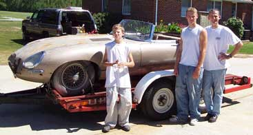 1963 Jaguar E-type on car trailer with family posing
